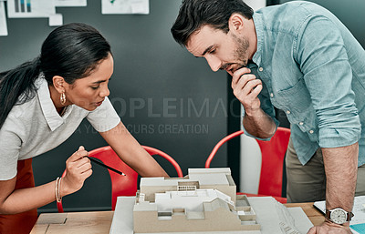 Buy stock photo Shot of two architects working together on a scale model of a building in an office