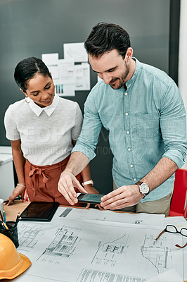 Buy stock photo Shot of two architects using a cellphone to take photos of blueprints in an office