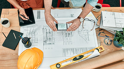 Buy stock photo Closeup shot of two unrecognisable architects using a cellphone to take photos of blueprints in an office