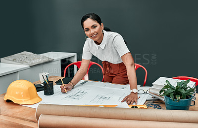 Buy stock photo Portrait of a young architect working with blueprints in an office