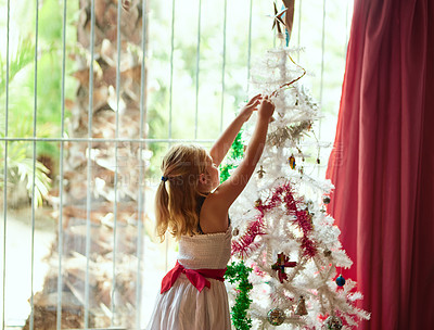 Buy stock photo Rearview shot of an adorable  little girl decorating a Christmas tree at home