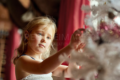 Buy stock photo Shot of an adorable little girl decorating a Christmas tree at home