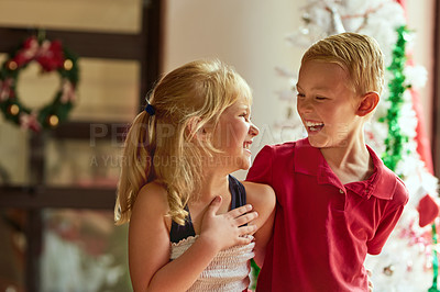 Buy stock photo Shot of two adorable young siblings having a laugh together at home on Christmas day
