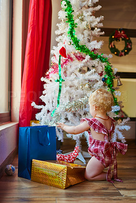 Buy stock photo Full length shot of an adorable baby girl opening presents near a Christmas tree at home