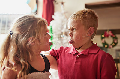 Buy stock photo Shot of two adorable two adorable young siblings making silly faces to each other at home