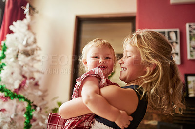 Buy stock photo Portrait of an adorable girl playing with her older sister at home on Christmas day