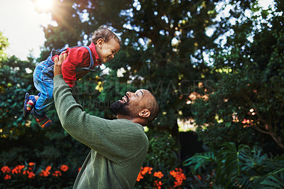 Buy stock photo Cropped shot of a handsome young man playing with his adorable son during a day out