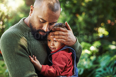 Buy stock photo Cropped shot of a handsome young man carrying and hugging his adorable son during a day out