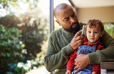 Buy stock photo Cropped shot of a handsome young man sitting outside and brushing his son's hair