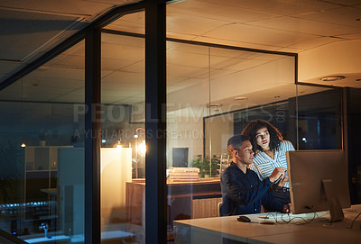 Buy stock photo Shot of a young businessman and businesswoman using a computer during a late night at work