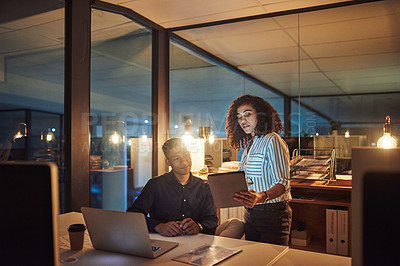 Buy stock photo Shot of a young businessman and businesswoman using a laptop and digital tablet during a late night at work