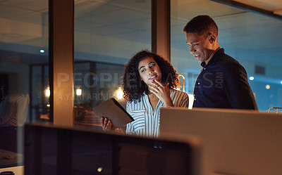 Buy stock photo Shot of a young businessman and businesswoman using a digital tablet during a late night at work