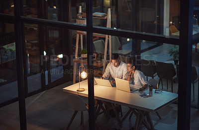 Buy stock photo Shot of a young businessman and businesswoman using a laptop during a late night meeting at work