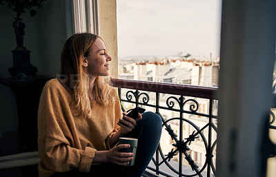 Buy stock photo Cropped shot of an attractive young woman sitting on a French balcony and holding a cup of coffee