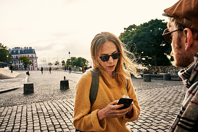 Buy stock photo Cropped shot of an attractive young woman standing with her boyfriend and using her cellphone while sightseeing in Paris