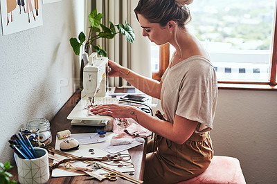 Buy stock photo Cropped shot of a young fashion designer using a sewing machine in her workshop