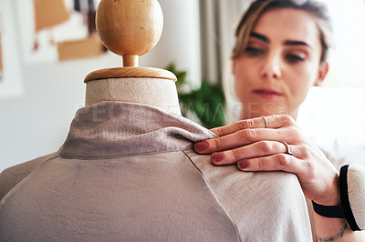 Buy stock photo Shot of a young fashion designer working on a garment hanging over a mannequin