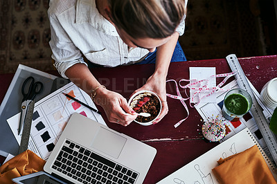 Buy stock photo Cropped shot of a fashion designer having breakfast while working at her desk
