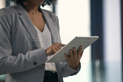 Buy stock photo Cropped shot of an unrecognizable businesswoman using a digital tablet while working inside her office