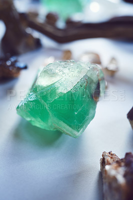 Buy stock photo Closeup of a beautiful green crystal placed on a table with other different types of crystals inside during the day