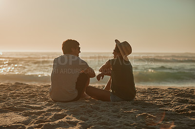 Buy stock photo Rearview shot of a happy young couple relaxing together on the beach at sunset