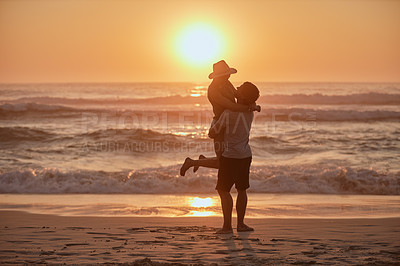 Buy stock photo Shot of a happy young couple enjoying a playful moment on the beach at sunset