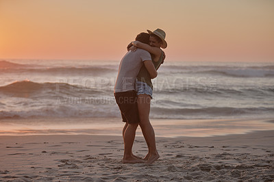 Buy stock photo Shot of a happy young couple hugging on the beach at sunset