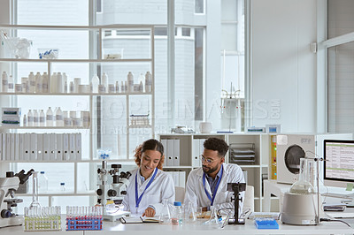 Buy stock photo Shot of two young scientists working together in a lab