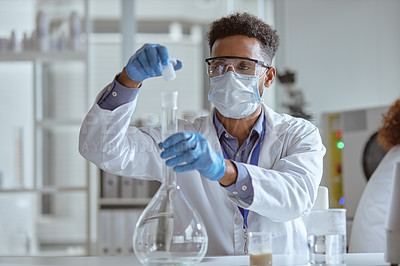Buy stock photo Shot of a young scientist conducting an experiment in a lab