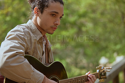Buy stock photo Cropped shot of a handsome young man standing alone and playing his guitar in the forest