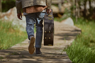 Buy stock photo Cropped shot of an unrecognizable man walking and carrying his guitar case during a day out in the forest alone