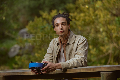 Buy stock photo Cropped shot of a handsome young man standing alone and holding his headphones during a day out in the forest