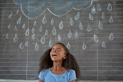 Buy stock photo Shot of a young schoolgirl standing in front of rain drawn on a black board