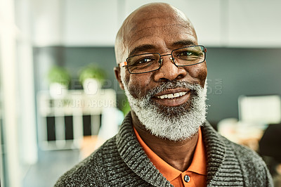Buy stock photo Cropped shot of a handsome mature businessman wearing glasses and standing alone in the office