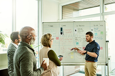 Buy stock photo Cropped shot of a diverse group of businesspeople standing and using a white board to strategise in the office