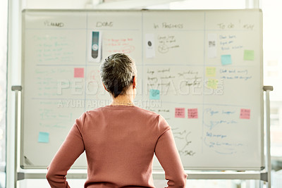 Buy stock photo Cropped shot of an unrecognizable businesswoman standing alone and looking at a white board in the office