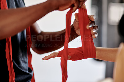 Buy stock photo Cropped shot of an unrecognizable female boxer getting her ands wrapped by her fitness coach in a gym