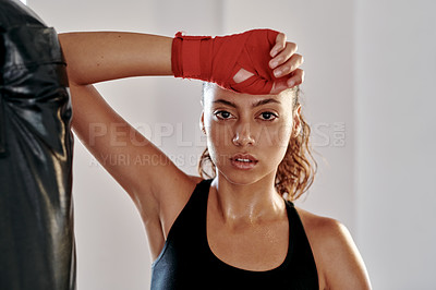 Buy stock photo Cropped portrait of an attractive young female boxer taking a break in a gym