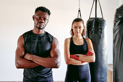 Buy stock photo Cropped portrait of an attractive young female boxer standing with her fitness coach in a gym