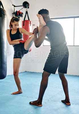 Buy stock photo Full length shot of an attractive young female kickboxer working out with her fitness coach in a gym