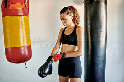 Buy stock photo Cropped shot of an attractive young female boxer putting on her gloves in a gym