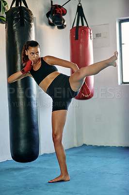 Buy stock photo Full length shot of an attractive young female kickboxer practicing in a gym