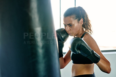Buy stock photo Cropped shot of an attractive young female boxer practicing with a punching bag in a gym