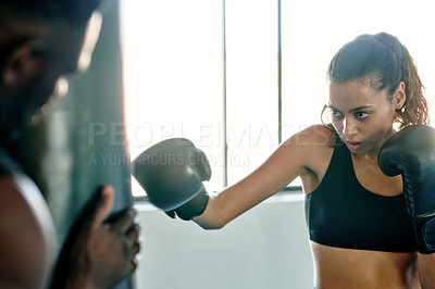 Buy stock photo Cropped shot of an attractive young female boxer practicing with her personal trainer in a gym