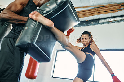 Buy stock photo Cropped shot of an attractive young female kickboxer practicing with her personal trainer in a gym