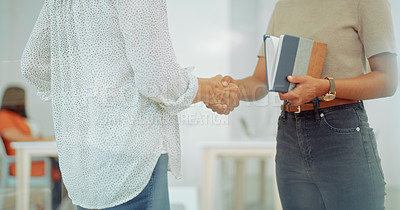 Buy stock photo Cropped shot of two businesswomen shaking hands in a modern office
