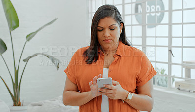 Buy stock photo Shot of a confident young businesswoman using a smartphone in a modern office