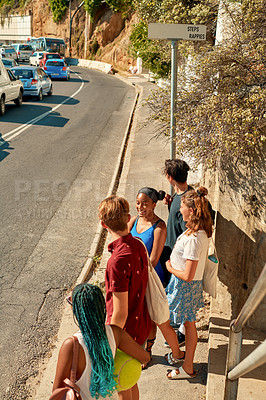 Buy stock photo Shot of a group of friends standing on the side of the road while waiting for traffic to pass