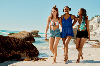 Buy stock photo Shot of three female friends enjoying themselves at the beach
