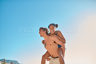 Buy stock photo Cropped shot of a young man piggybacking his girlfriend on the beach
